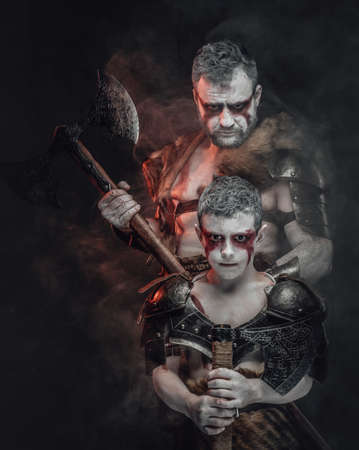 Portrait of a military tribal family a little warlike kid and his father behind him they armed with axes and posing in dark background. Stock fotó