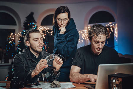 Serious group of three people analyzing eyewear and fossil sitting at table there different tools and laptop in living room decorated with xmas tree Foto de archivo