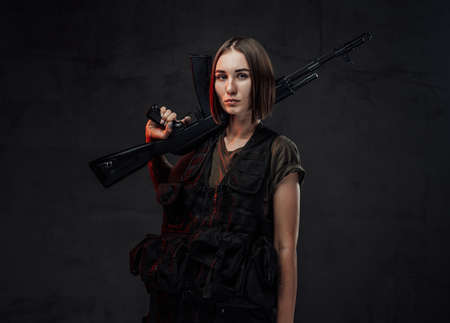 Beautiful woman with short haircut dressed in black armour with dark shirt holding assault rifle in dark background.