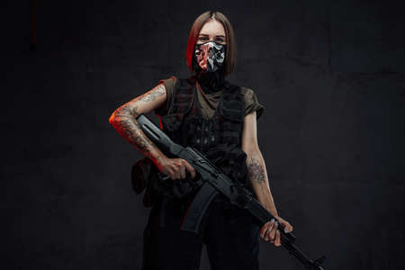 Armed with ak74 rifle and weared with mask stylish female mercenary poses in dark background.
