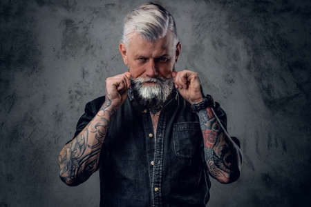Portrait of old and confident man with tattooed body and gray hairs which poses in dark background.