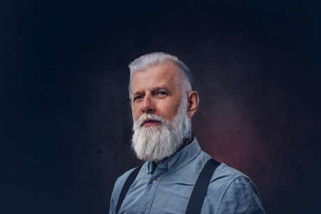 Portrait of elegant and stylish grandfather with modern hairstyle in shirt which poses in dark background.