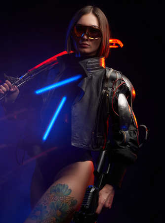 Portrait of a cyber woman with sword on her shoulder and rifle in dark background. Stylish and dangerous female soldier with sunglasses dressed in black jacket.