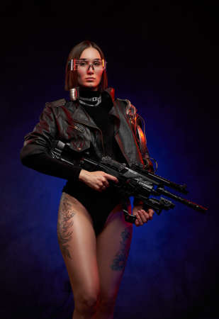 Martial and futuristic woman with implant and glasses posing in studio. Portrait of a attractive and female soldier in black clothing with glasses and tattooed legs in dark background. Banque d'images