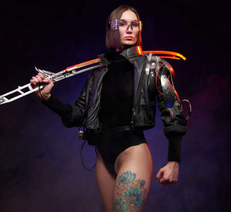 Martial portrait of a female warrior armed with futuristic and glowing sword and weared with eyewear. Beautiful woman in cyberpunk style dressed in black jacket with cybernetic shoulder.