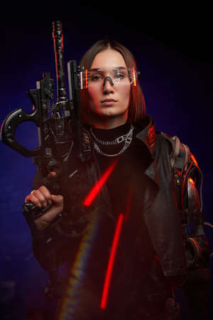 Futuristic portrait of a attractive female mercenary with fashionable style posing in dark background with rifle. Martial woman in cyberpunk style dressed in black clothing.