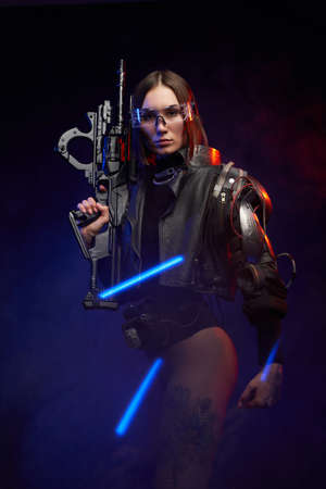 Atmospheric portrait of a female soldier with nude legs and eyewear posing in dark background with blue lights. Cyber woman with implant on her shoulder looking at camera.