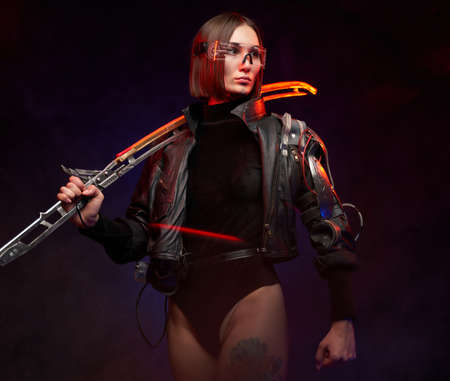 Fashionable woman killer with short haircut holding futuristic sword on her shoulder. Martial woman in black costume with eyewear posing in dark background with lights.