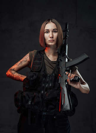 Dressed in black armour with dark shirt martial woman with short haircut poses in dark background holding assault rifle. Banque d'images