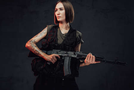 Dressed in dark armour military woman with short haircut and bandaged hand holds her assault rifle in dark smokey background.