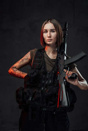 Holding assault rifle martial woman in black armour with short haircut poses in dark background.