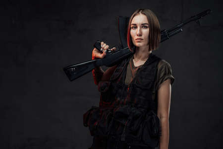 Dressed in black armour with dark shirt martial woman with short haircut poses in dark background holding assault rifle. Imagens