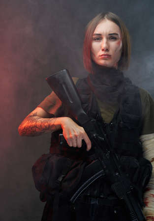 Atmospheric portrait of military woman which dressed in armour with bandaged arm and short haircut holding rifle in smokey background. Banque d'images