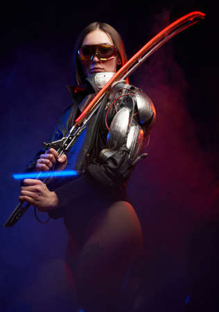 Atmospheric portrait of a beautiful female assassin posing in dark background with smoke. Armed with glowing sword military woman with sunglasses and implant.