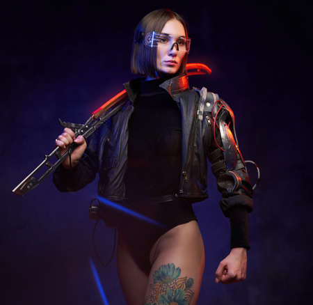 Stylish and at the same time dangerous woman assassin from future with glowing sword. Female soldier in cyberpunk style with implant and glasses.