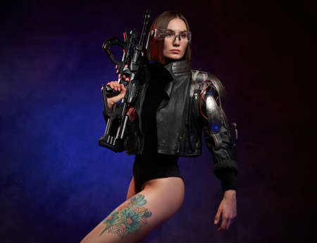 Stylish and beautiful woman with cybernetic hand posing in dark background with spotlight. Dangerous female soldier with short haircut holding rifle.