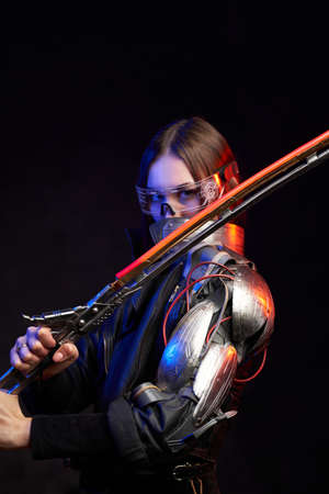 Futuristic female fighter with glowing sword and eyewear in black background. Attractive military woman looks at camera hiding her face behind collar.