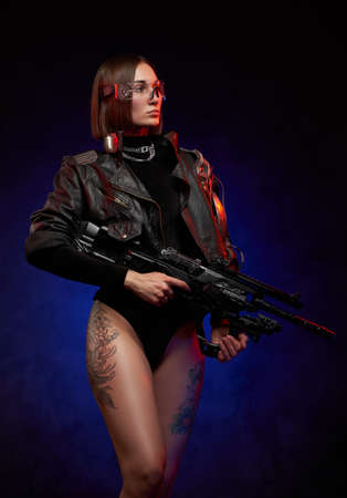 Brown haired female mercenary dressed in black jacket and posing with nude and tattooed legs. Portrait of a beautiful martial woman in cyberpunk style with glasses and short haircut. Imagens