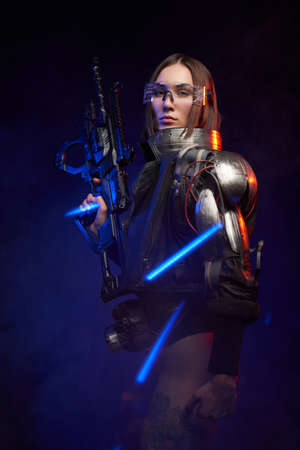 Tattoed martial woman in cyberpunk style dressed in stylish black clothing. Fashionable and sexy female soldier holding a futuristic rifle and posing in dark background with blue lights. Imagens