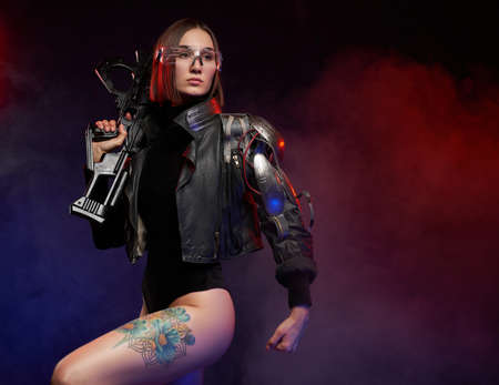 Female warrior in cyberpunk style poses in dark background. Seductive and slim woman with glasses and cybernetic hand dressed in black jacket.