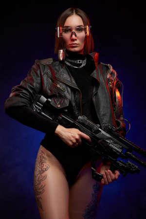 Brown haired female mercenary dressed in black jacket and posing with nude and tattooed legs. Portrait of a beautiful martial woman in cyberpunk style with glasses and short haircut. Banque d'images
