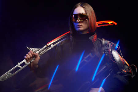 Serious military woman in stylish dark clothing and with implant on her shoulder poses in dark background. Attractive female soldier holding a glowing sword on her shoulder and a rifle.