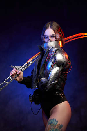 Futuristic female fighter with glowing sword and nude tattooed legs in dark blue background. Attractive military woman looks at camera hiding her face behind collar. Banque d'images