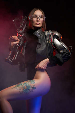 Attractive and sexy female soldier dressed in black jacket poses in dark background. Stylish woman with short haircut and glasses holding futuristic rifle.