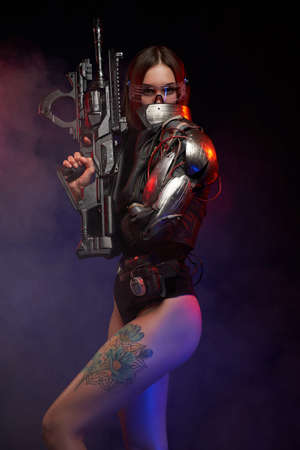 Cyber woman with implant on her shoulder and hand holding a rifle poses in dark background. Sexy and martial woman with nude and tattooed legs in studio. Imagens