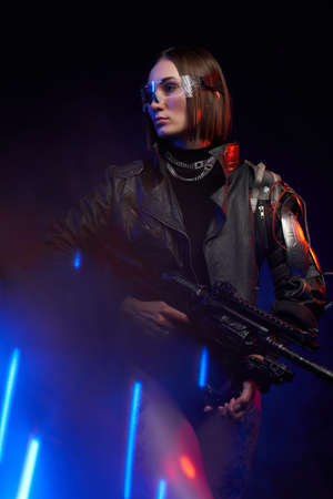 Tattooed female soldier with eyewear and modern hairstyle poses in dark background with lights. Glamour and at the same time dangerous woman with cybernetic shoulder.