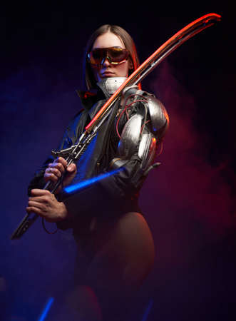 Cybernetic female assassin with sunglasses dressed in black jacket holding a glowing sword. Futuristic martial woman with short haircut posing in dark background.