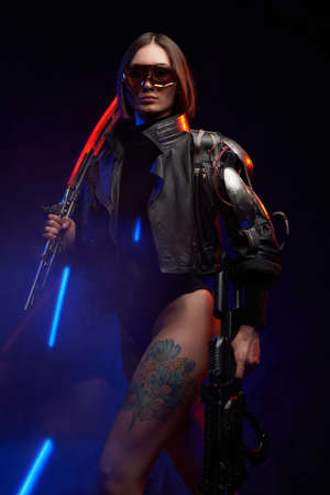 Fantasy portrait of a attractive female soldier with short haircut holding a futuristic sword on her shoulder and gun. Dangerous woman in cyberpunk style going in dark background.