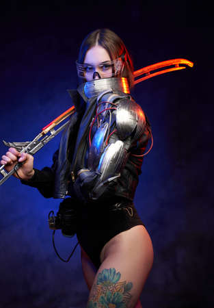 Futuristic female fighter with glowing sword and tattooed legs in dark blue background. Attractive military woman looks at camera hiding her face behind collar.