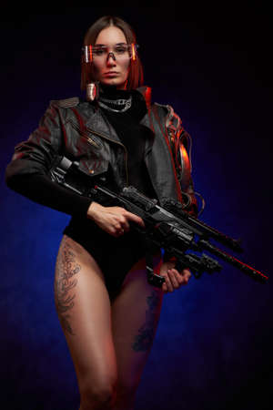 Martial and futuristic woman with implant and glasses posing in studio. Portrait of a attractive and sexy female soldier in black clothing with glasses and tattooed nude legs in dark background. Banque d'images