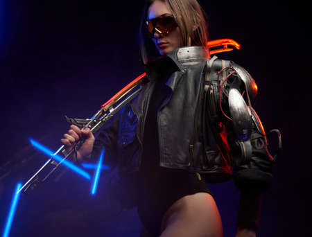 Beautiful woman with implant wearing black clothing and sunglasses in dark background. Female mercenary holding a glowing sword on her shoulder.