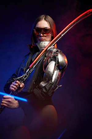 Posing in dark background military woman with sunglasses and glowing sword. Female assassin from the future in black stylish clothing with cybernetic shoulder.