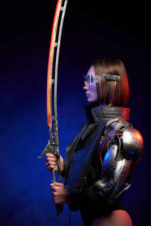 Seductive female assassin poses in dark background looking at her glowing sword. Profile of a military woman from the future in cyberpunk style.