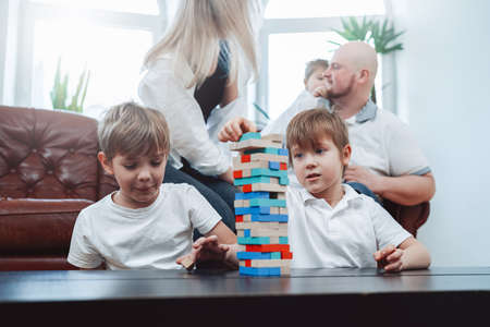Weekend of happy caucasian family in modern apartment. Two little boys play jenga game competing who is better. Banque d'images