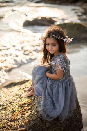 Portrait of journey of a little girl in thailand. Preteen girl in dress poses sitting on the rock barefot looking away in the sunshine.