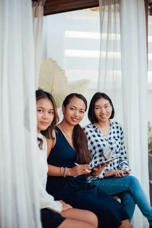 Creative work of female designers. Three asian girls in formal clothing pose on doorstep looking at camera and smiling.
