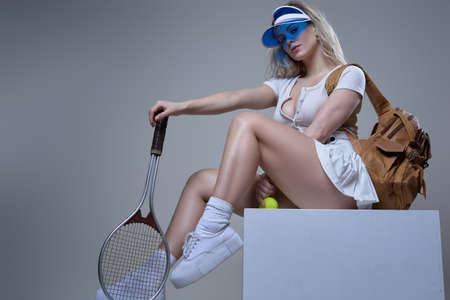 Portrait of pretty and young sportswoman with blue cap and blond hairs posing in white background holding tennis racket and ball.