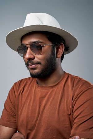Closeup headshot of a fashionable hindu macho with hat and sunglasses posing in gray background.