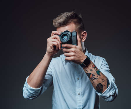 Stylish photographer with tattooed hand does shot using his photo camera. Professional portrait of a young man.