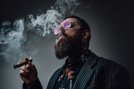 Elegant man in retro style poses in dark background smoking cigar. Portrait of a bearded guy with stylish coiffure.