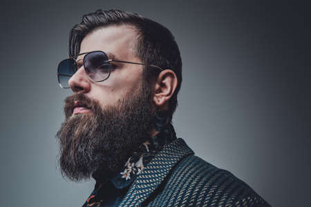 Portrait of a fashionable hipster person wearing modern and luxurious clothing. Bearded man poses in gray background.