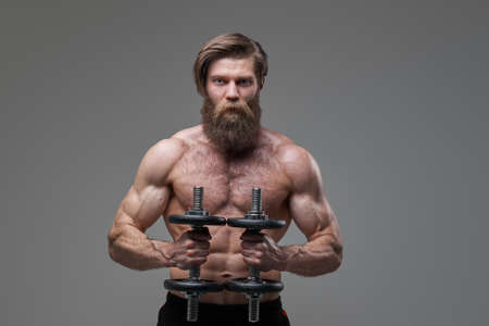 Athletic man with fashionable hairstyle and dumbells in studio