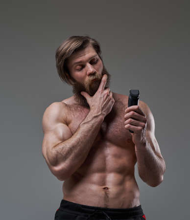 Thoughtful bodybuilder holding a hair clipper in gray background Фото со стока