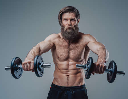 Strong bodybuilder with dumbells and torso posing in studio Stock Photo