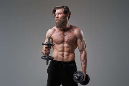 Muscular guy with dumbells looks away holding dumbells