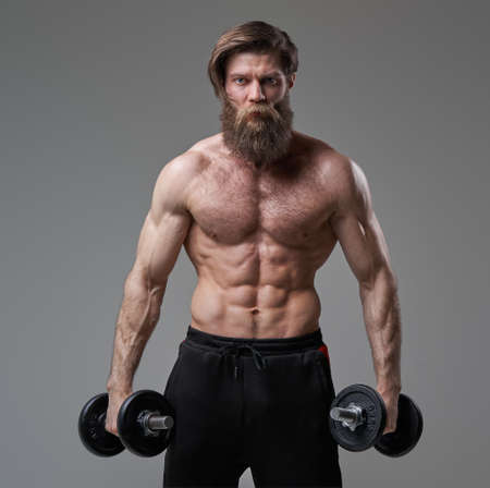 Brutal guy with muscular build posing in gray background with dumbells